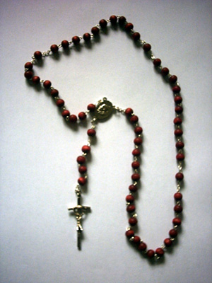 A chain of Rosary beads have a Cross, a large bead above it, three small beads, a medal honoring a particular Saint, and five large beads separating each decade of ten smaller beads.