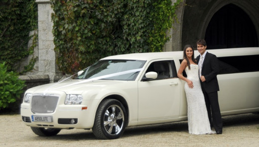 Bride and Groom Standing By White Wedding Limo