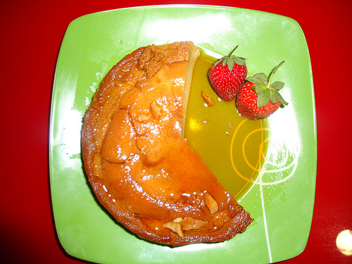 Flan served with whole strawberries.
