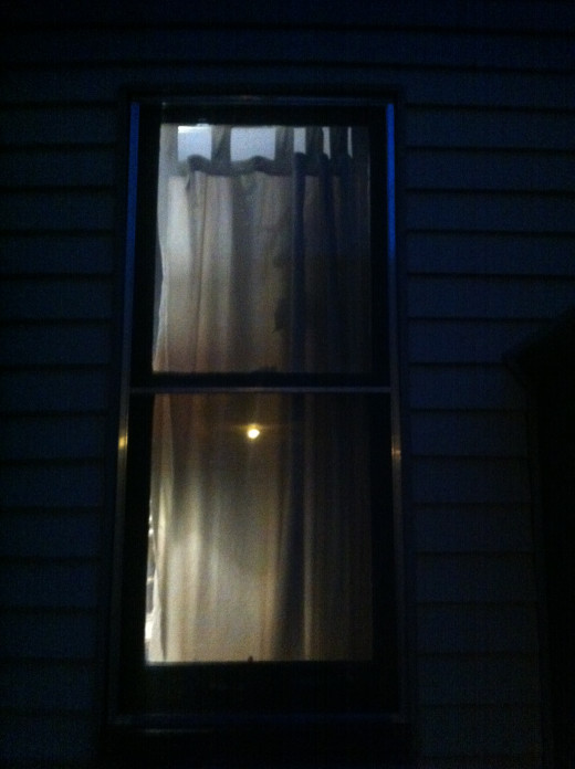 A light seen on the inside of a home at night.