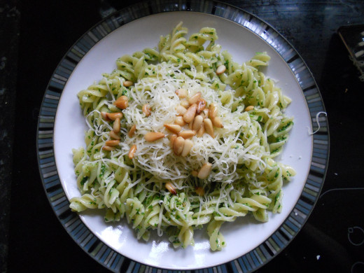 Pasta served with rocket pesto, grated cheese and toasted pine nuts