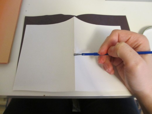 Fold the white paper in half and paint the spine with glue.