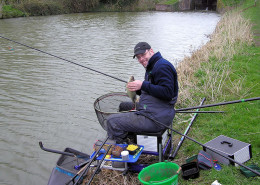 An angler with his catch on a canal in Devises England