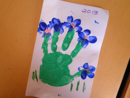 A childs hand-print with grass growing under the flower art. This is also a cute way to finish off your project. Great job Lyzaea! (4 years old)