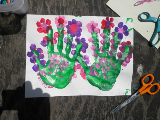 A very creative hand-print piece of art! This child had so much fun with the thumb print part that they added on even more flowers throughout their hand-print! Super cute!