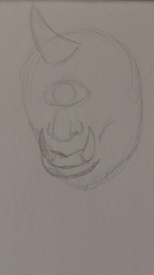 Now loosely sketch in the nose and mouth with a couple of teeth as shown