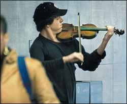 Man playing violin at Washington D.C. Metro station.