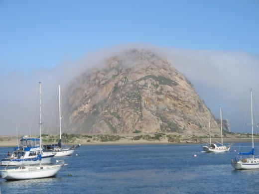 Morro Rock covered in a layer of fog.