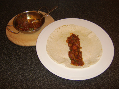 A tortilla wrap is filled with leftover pork in homemade Bhuna sauce