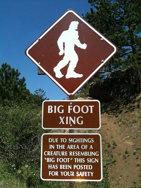 A street sign humorously warns drivers to watch for Bigfoots (Bigfeet?) crossing the street.
