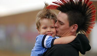 Single dad kissing baby