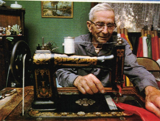 Ansel Toney at his sewing machine making a kite