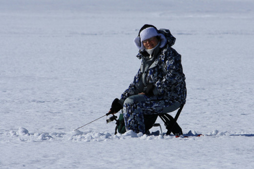 A women fishes in a hole on the ice in a special chair.