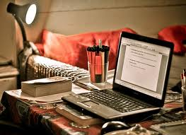 A laptop and a glass of water to think with a clear mind when writing