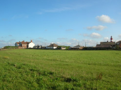 Happisburgh, small coastal village in Norfolk. View from the car park across to the lighthouse.