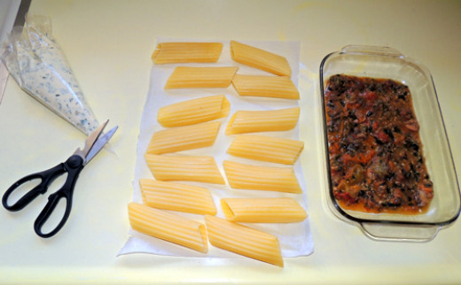 mise en place to assemble the manicotti - snip off end of pastry bag