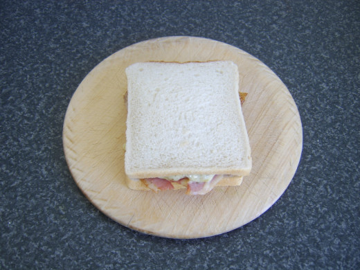 Top is placed on turkey, bacon and melted cheese sandwich