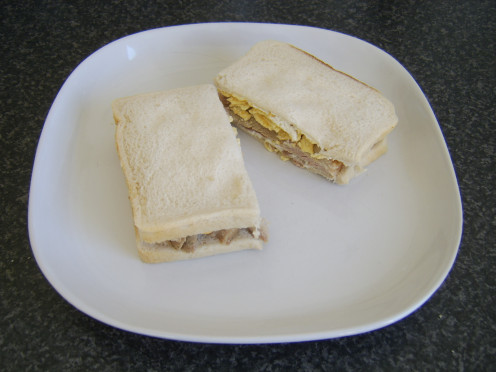 A simple sandwich of cream cheese, sliced turkey thigh and potato chips/crisps