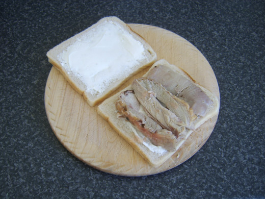 Turkey thigh slices are laid on one slice of bread