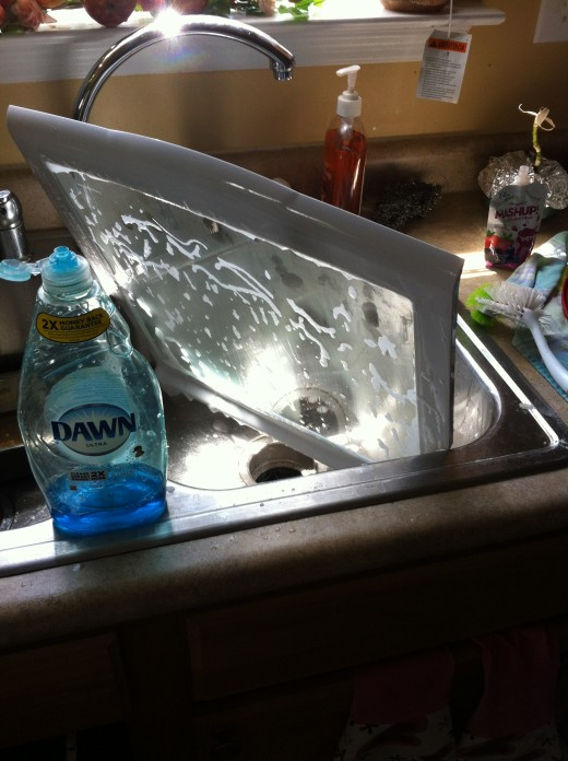 Washing the top shelf with dishwashing liquid soap, then with glass cleaner.