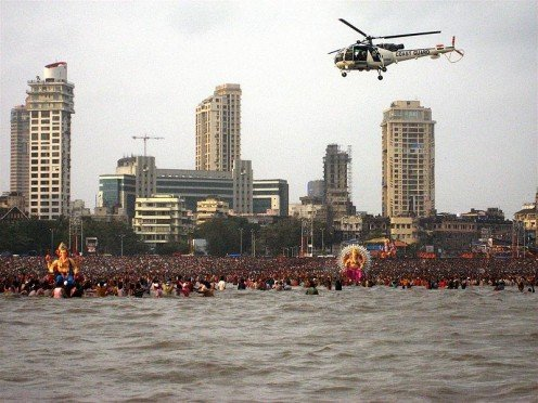 An Indian Cost Guaard Helicopter patrols a Ganesh Visarjan ritual at Chowpatty Beach, Mumabi