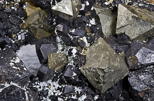 Magnetite (the black and grey mineral) and pyrite (the gold mineral). Magnetite is found in many magnetotactic bacteria.