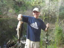 Catching a nice large mouth bass using a spinning rod and reel while fishing from the bank.