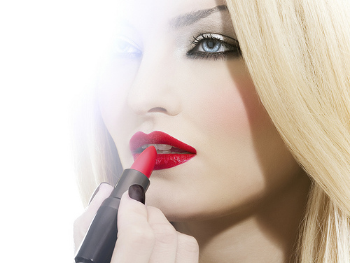 Women apply lipstick perfectly in the mirror of a public restroom while failing to clean up after themselves.
