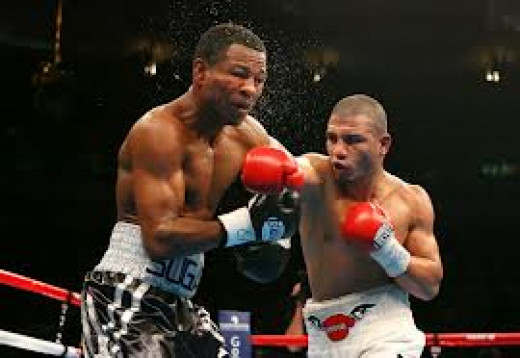 Sugar Shane Mosley takes a bomb from Miguel Cotto. Cotto won the bout by 12 round decision but it was hard fought and went down to the wire.