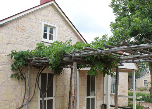 A natural grape arbor enhances this old historical home