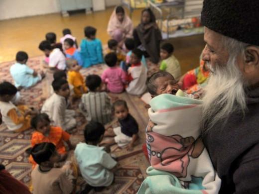 Addul Sattar Edhi holding a new born child.