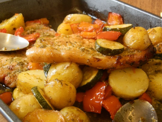 lemon pork chops and roasted vegetables in oven dish