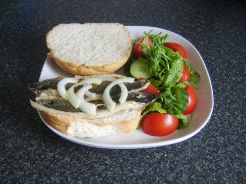 Rollmop style herring kebabs are served on a bread roll with a simple salad