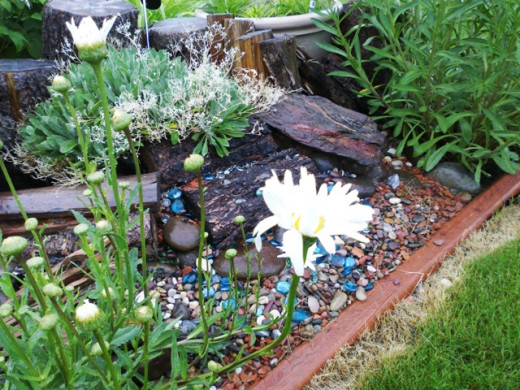 This raised bed was made from rocks, pebbles, pieces of wood, and a few glass beads.