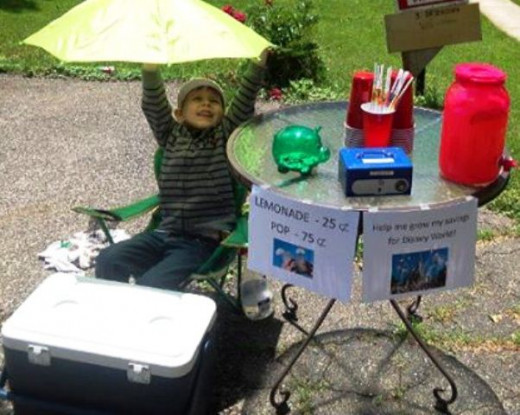 A tiny entrepreneur sells drinks at a yard sale.