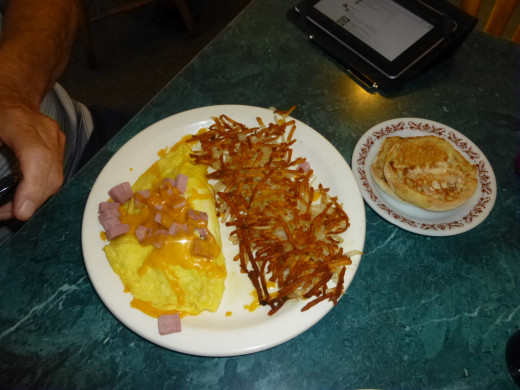 A  delicious omlette with hashbrown potatoes and an english muffin.