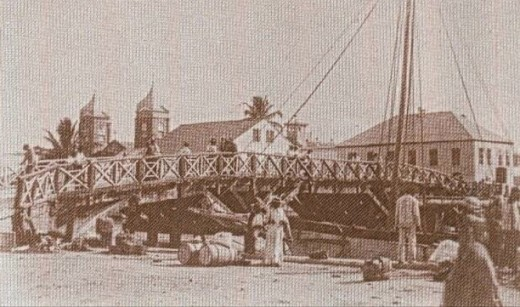 Belize City's original swing bridge in 1923. A newer version, painted yellow, cuts the city in half into North and South sections.