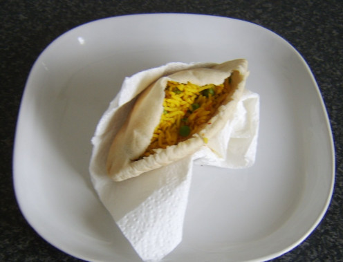 Indian spiced rice is spooned in to a pitta bread pocket