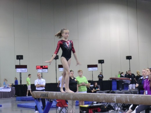 Young gymnast on the beam exercise