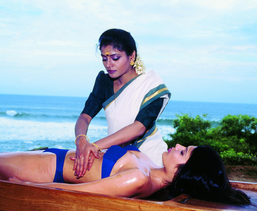 An Ayurvedic massage therapist plies her craft.