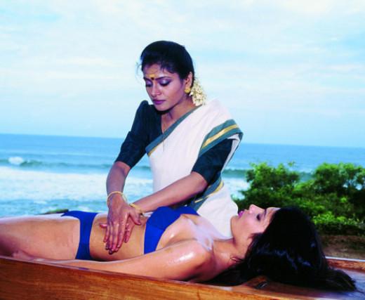 An Ayurvedic massage therapist plies her craft.