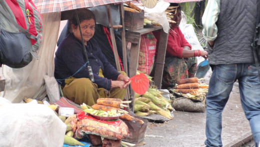 Local Nepali street vendor selling roasted maize in a rainy day in Darjeeling