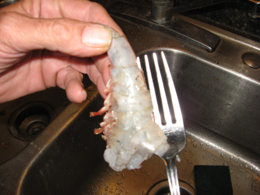 Use a fork to peel and devein shrimp.