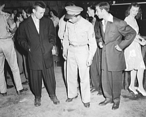 A serviceman appears to be intrigued by some youths in Zoot suits. 1942