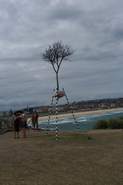 """fragment"" by Kevin Draper WA. This sculpture envolved from a series of works using tripod structures integrated with symbolic plant forms.  The tripod acts as an isolating device suspending the tree symbol between land and the sky."