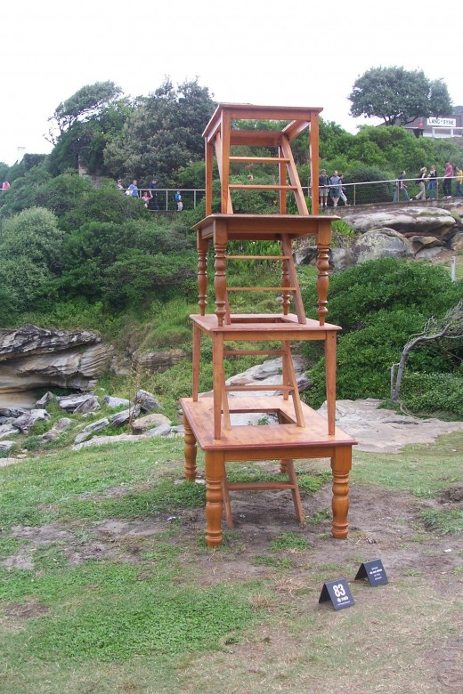 """social climbing"" by Louisa Dawson, made from wood.  This tower of tables, joined with a staircase, explores the social functions of the dinner table, suggesting moving up the dinner table or escaping out the bottom."