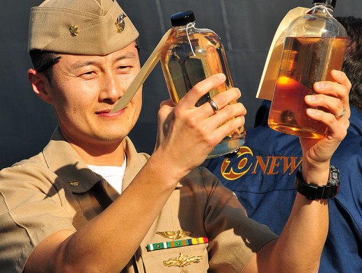 US Naval Officer compares sample bottles of traditional diesel fuel marine and an algae-derived alternative fuel