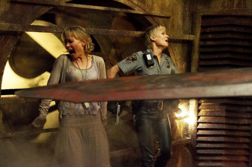 Rose and Cybil stuck in a room while Pyramid Head threatens them with his Great Knife.