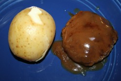 Gravy smothered hamburgers, with a side of boiled potatoes