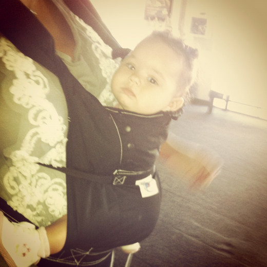 Ergo Baby Carrier, wearable in 3 positions & comes with a sleep hood.  Perfect for airplane travel.